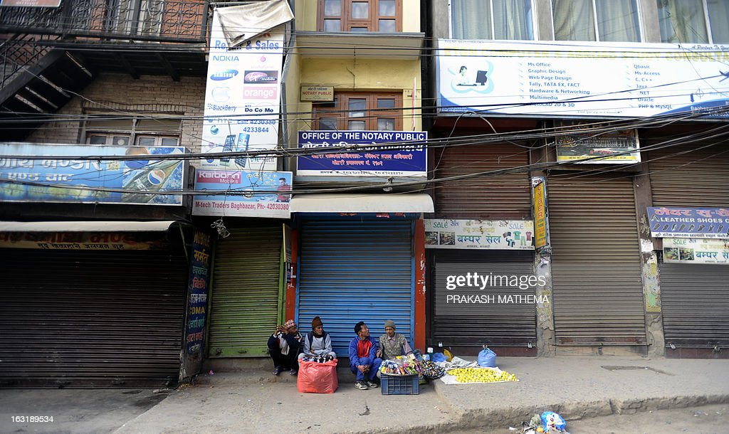 Street vendors sit on the sidewalk in front of closed shops during a general strike called by the Communist Party of Nepal-Maoist in Kathmandu on March 6, 2013. The nationwide strike was organised by a hardline breakaway faction of the country's ruling Maoists in protest over an attempt by the mainstream political parties protest against an agreement to allow the Chief Justice Khil Raj Regmi of the Supreme Court to head the new administration to oversee the vote in May or June. AFP PHOTO/Prakash MATHEMA