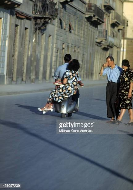 A street view as a couple ride a Vespa in Florence Italy