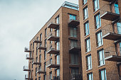 Modern brick apartment buildings with individual balconies extending from walls under overcast sky