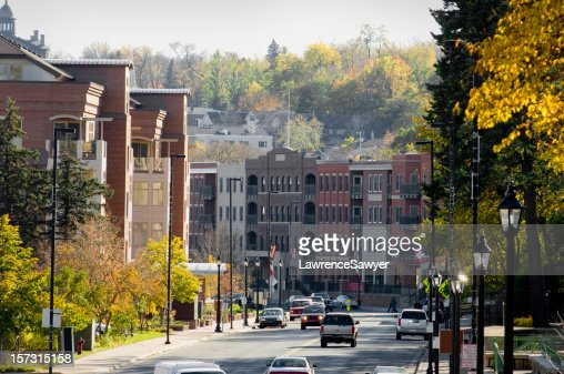Street view of house building and green tress in Autumn