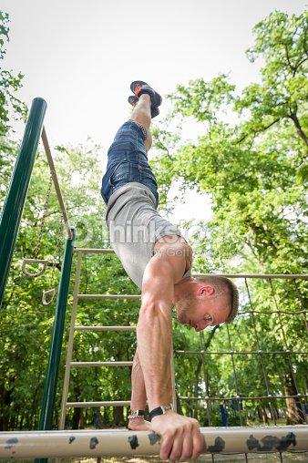 Street workout men handstand in a park