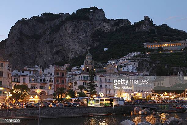 Streetlights illuminate waterfront buildings at dusk on July 29 2011 in Amalfi Italy The Amalfi coastline is among Italy's most popular tourist...