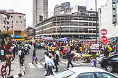 Lagos Island's commercial district, businessmen and market people crossing the street.