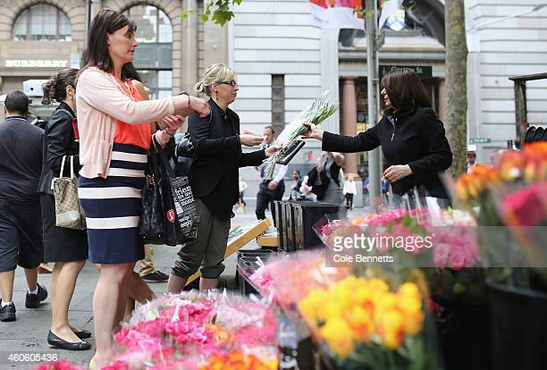Streetside florists sell flowers to be placed at the massive floral tribute in the Centre of Martin Place on December 18 2014 in Sydney Australia...