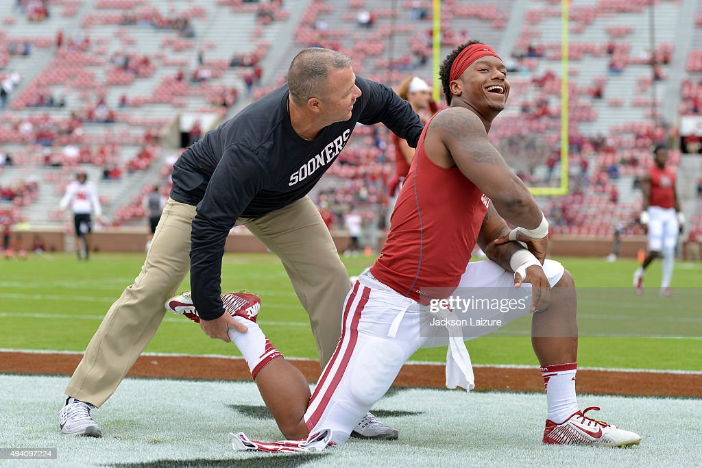 Strength coach Jerry Schmidt stretches running back Joe Mixon #25 of the Oklahoma Sooners before their game against the Texas Tech Red Raiders on October 24, 2015 at the Gaylord Family Oklahoma Memorial Stadium in Norman, Oklahoma.