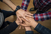 Group of young people with their hands together.