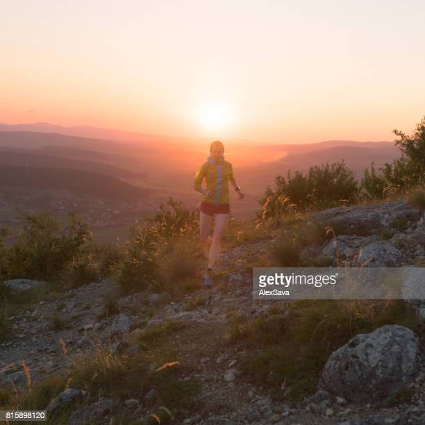 Strenuous female athlete trail running on rough terrain during sunset