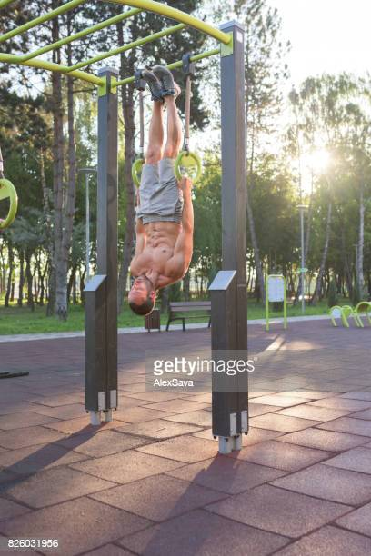 Strenuous man doing calisthenics workout on rings outdoor