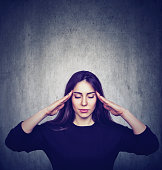Stressed anxious woman with headache isolated on gray grunge wall background