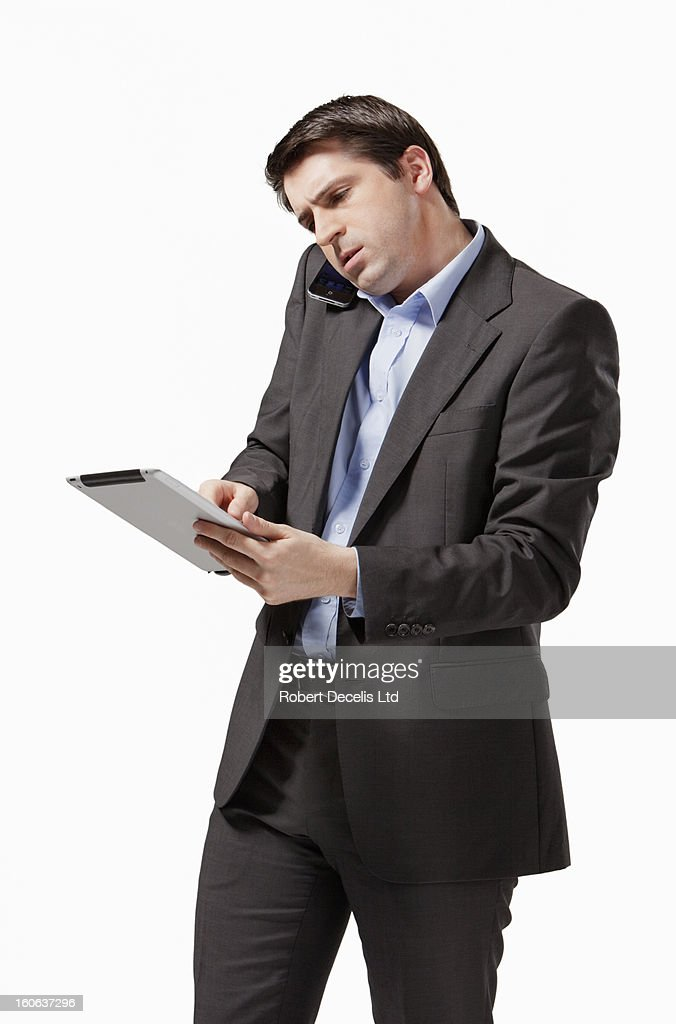 Stressed business man using smart phone and tablet : Stock Photo