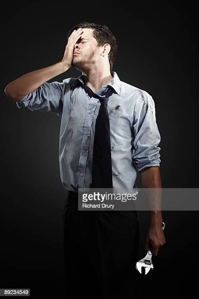 Stressed businessman holding wrench