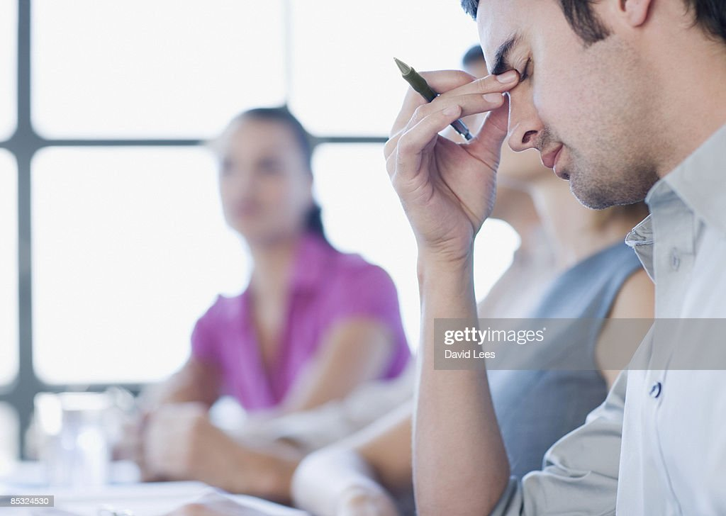 Stressed businessman in meeting  : Stock Photo
