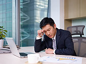 """asian businessman sitting in office, looking tired. click for more: abusiness peopleai"""
