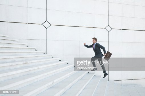 Stressed Businessman Running Up White Staircase Outdoors