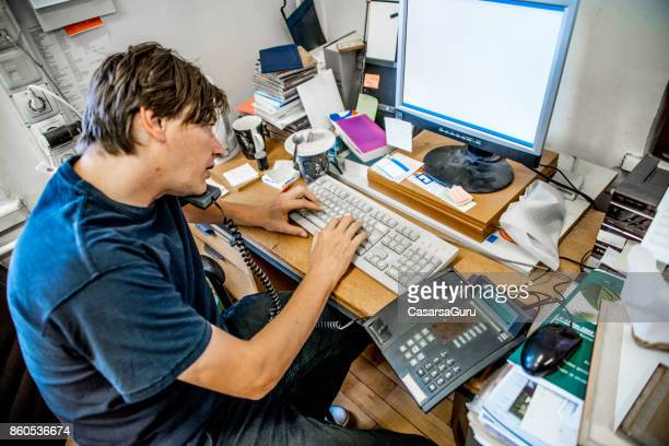Stressed Businessman Sitting At Desk In Office Working On Computer