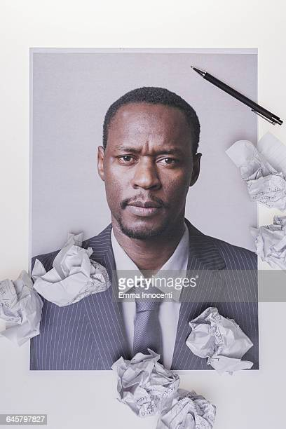 Stressed businessman surrounded by crumpled paper