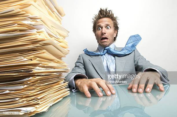 Stressed Businessman Terrified at Pile of Documents