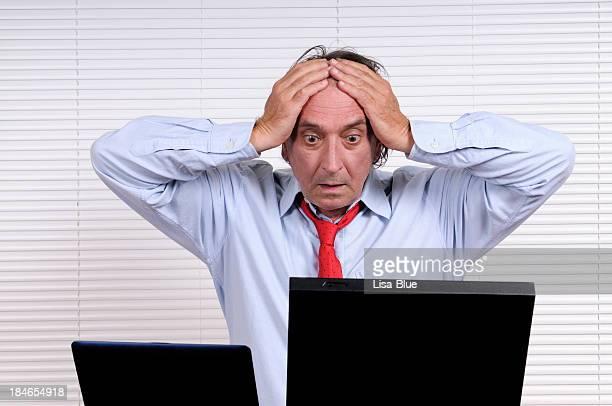 STRESSATO Uomo d'affari con la testa tra le mani cercando PC
