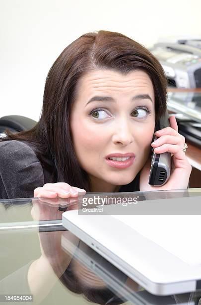 ストレスのたまった電話で話しているビジネスウーマンに隠れて、デスク