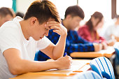 Stressed college student  for exam in classroom