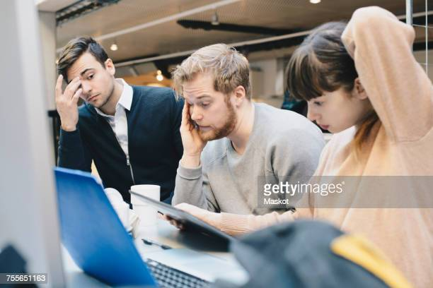 Stressed computer programmers using digital tablet at desk in office