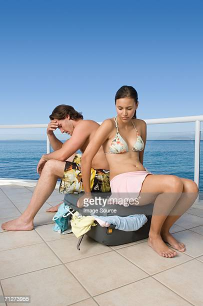 Stressed couple with suitcase