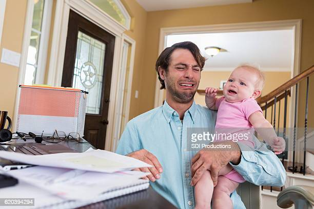 Stressed dad with baby working from home