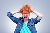 Woman with red hair holding her head shouting. Stress and hysterical. negative emotions. Studio shot. Gray background