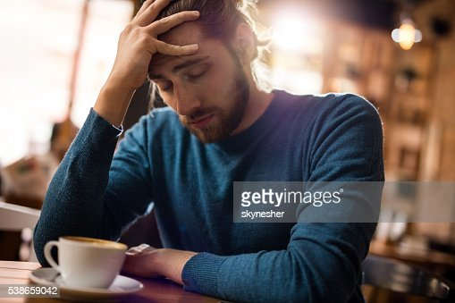 Stressed man holding his head in pain in a cafe. : Stock Photo