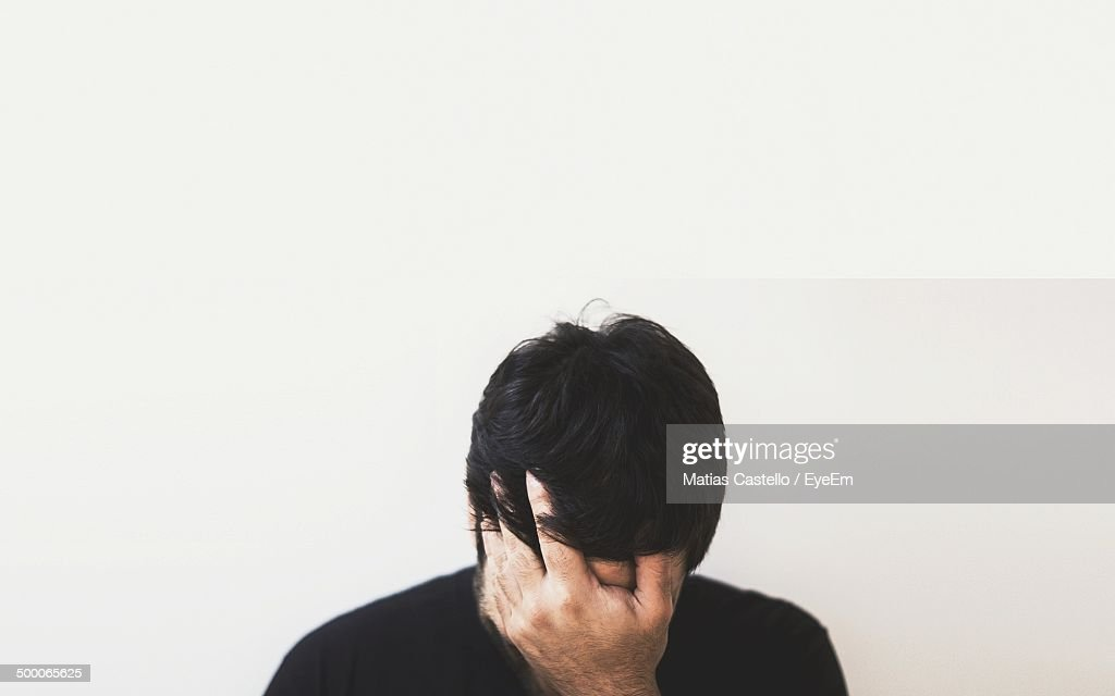 Stressed man sitting against wall