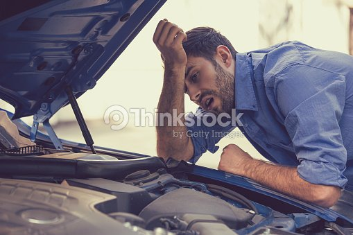 stressed man with broken car looking at failed engine : Stock Photo
