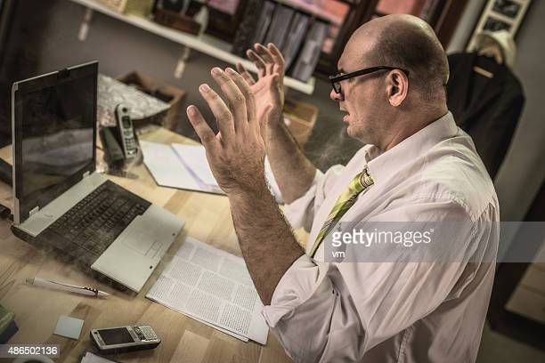 Stressed mature adult businessman using laptop computer