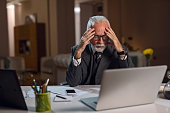 Worried senior businessman feeling stressed while reading e-mail on laptop in the office.