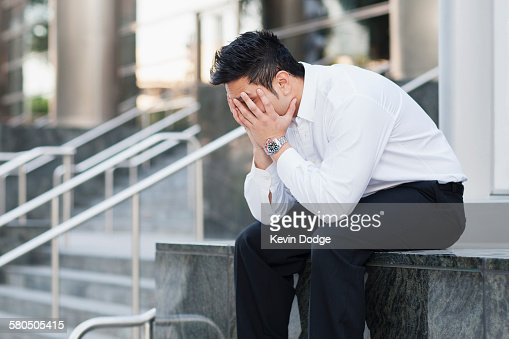 Stressed mixed race businessman covering his face : Stock Photo