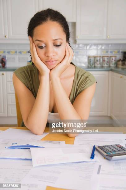 Stressed mixed race woman examining bills in kitchen
