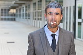Stressed out businessman smoking four cigarettes at the same time.
