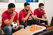 Portrait of a group of three friends and soccer fans feeling worried while watching a game on TV