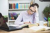 Stressed student  Doing  Homework At The Desk