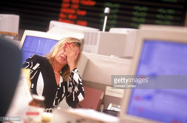 Stressed trader sitting at her desk