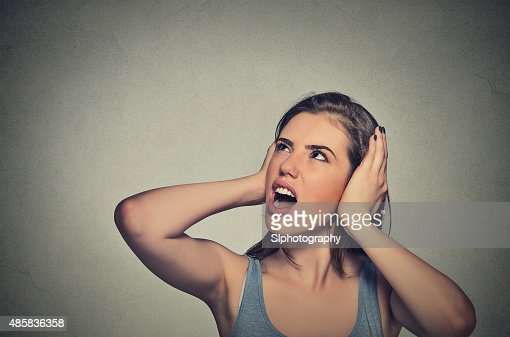 stressed woman covering her ears looking up : Stock Photo