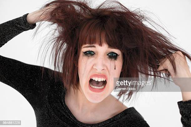 Stressed woman pulling her hair, screaming
