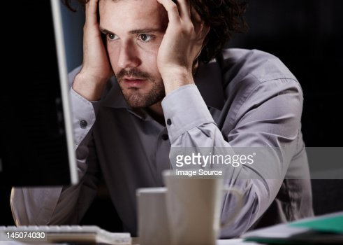 Stressed young man, working late