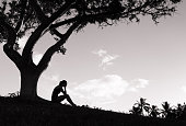 Silhouette of stressed young women sitting under the tree.