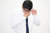 Tired businessman holding eyeglasses and rubbing his eyes
