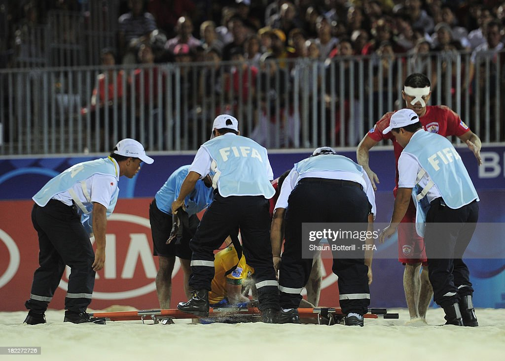 Stretcher bearers tend to a player during the FIFA Beach Soccer World Cup Tahiti 2013 3rd Place Playoff match between Brazil and Tahiti at the Tahua To'ata stadium on September 28, 2013 in Papeete, French Polynesia.