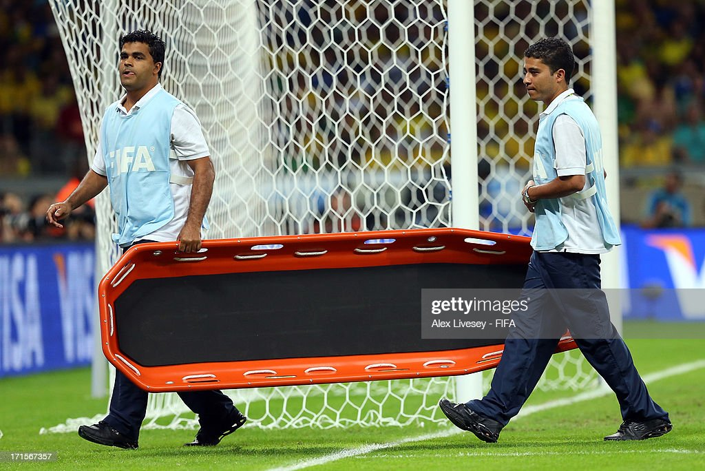 Stretcher bearers walk off the pitch during the FIFA Confederations Cup Brazil 2013 Semi Final match between Brazil and Uruguay at Governador Magalhaes Pinto Estadio Mineirao on June 26, 2013 in Belo Horizonte, Brazil.
