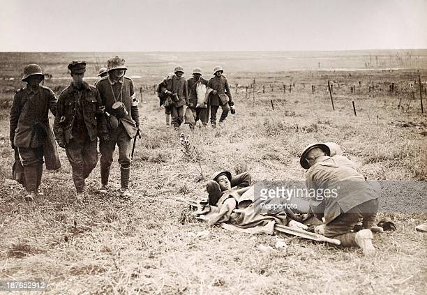 A stretcherbearer tending to an injured soldier amidst other wounded servicemen and prisoners of war during the Battle of the Somme in World War One...