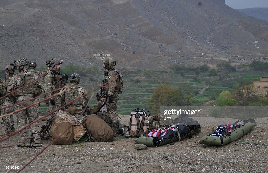 Stretchers bearing the remains of two US soldiers are seen draped with the US flags near the scene of a helicopter crash in the Pachir Wa Agam district of Nangarhar province on April 9, 2013. A NATO helicopter crashed in eastern Afghanistan on Tuesday killing two US troops, officials said, adding there was no insurgent activity in the area at the time of the incident. Taliban militants said they had shot down the helicopter, but the group often makes exaggerated claims of success on the battlefield against NATO forces and the US-backed government. AFP PHOTO / Noorullah Shirzada