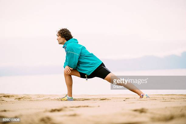 Stretching after training in summer on beach in sunset
