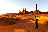 Teenage girl wearing a winter hat, mittens and coat stretches outdoors on rippled sand at the Totem Pole rock formations at sunrise, Monument Valley, Arizona, USA